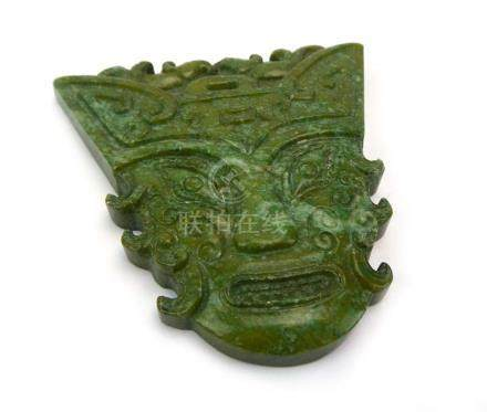 An Eastern green hardstone carving/pendant modelled as a masked figure, l. 7.