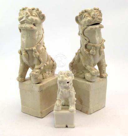 A pair of Chinese blanc de chine figures, each modelled as a foo dog on a square plinth,