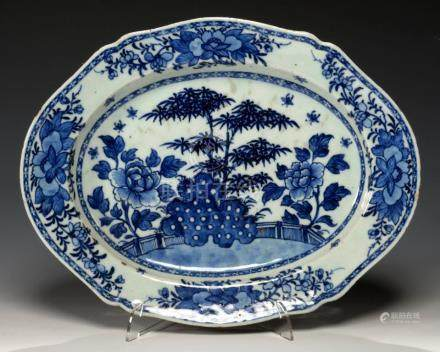 A CHINESE EXPORT PORCELAIN SHAPED OVAL BLUE AND WHITE DISH, C1780 painted with bamboo, peony and