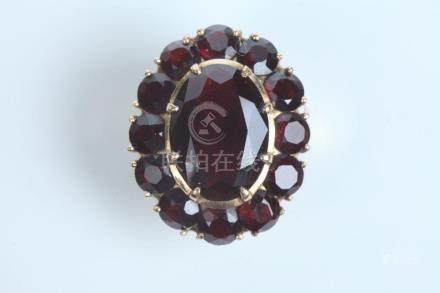 18K YELLOW GOLD AND GARNET OVAL RING. - Ring size: 5 1/2.