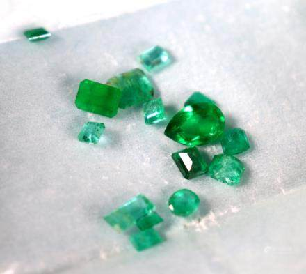 15 Small Faceted Emeralds; 1 Larger Pear Shape