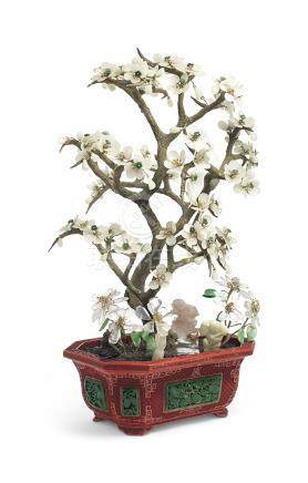 AN EMBELLISHED HARDSTONE MODEL OF A TREE IN A SPINACH-GREEN JADE-INSET CARVED RED LACQUER JARDINIÈRE