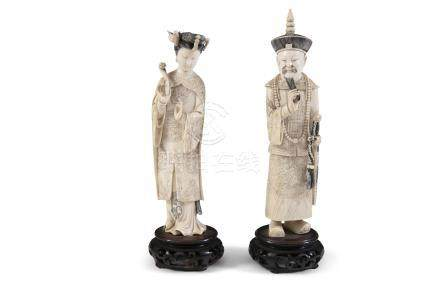 A PAIR OF CHINESE CARVED IVORY STANDING FIGURES, modelled as a manchu male and female, he stands