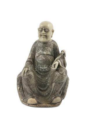 A CHINESE 18TH CENTURY SOAPSTONE FIGURE, seated holding a fly whisk, his robe incised and inked