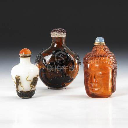 3 Snuffbottles - Glas und Überfangglas.Three Glass and Overlay Snuff Bottles, some with Buddhist and