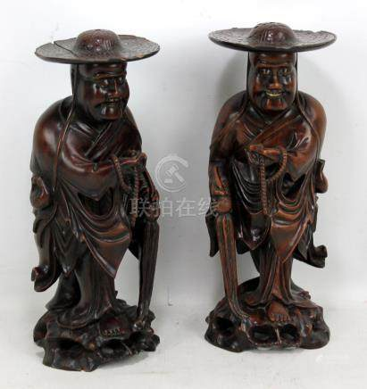 An opposing pair of 19th century Chinese carved root wood figures of Mahayana monks holding beads,