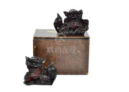 A pair of Chinese cherry amber models of Buddhist lion dogs, one with ball, the other with cub, each