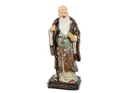 A 20th Century Chinese porcelain figure of a scholar, holding a scroll and staff (missing top of