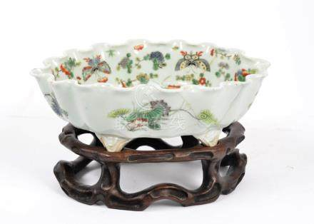 A Chinese canton glazed bowl, decorated with flowers and butterflies, placed upon a carved wooden