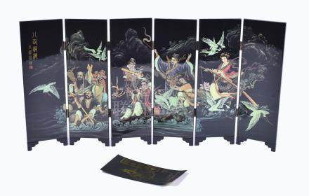 A modern Chinese lacquered folding table screen depicting the Eight Immortals crossing the sea,