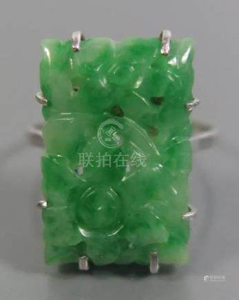 A Carved Jadeite Ring in a platinum or gold setting, marks rubbed, size N, 4.4g