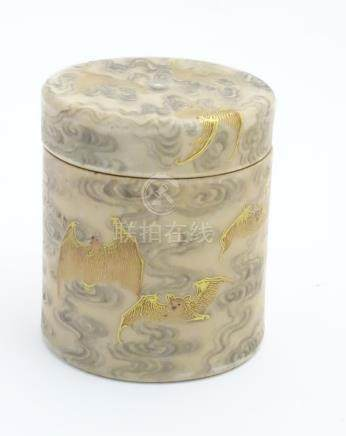 A Chinese lidded pot decorated with bats in flight with gilt highlights.