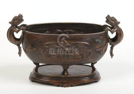 A Chinese oval bronze censor on stand. With twin handles formed as Kylin, decorated with relief work