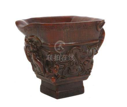 A large Chinese horn libation cup. With a scrolling handle and carved with mythical beasts