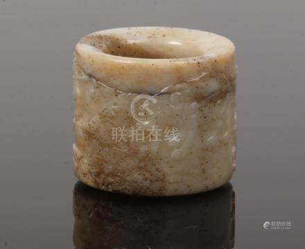 A Chinese mutton fat jade archers ring. Carved in low relief with a continuing band of animals in