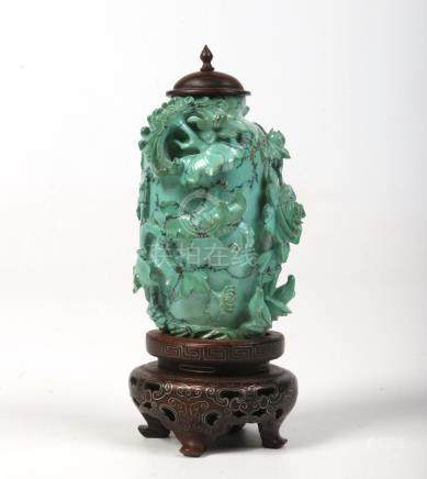 A Chinese Qing dynasty miniature turquoise jar with hardwood cover and raised on a hardwood plinth