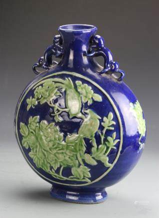 18th C., blue glazed moon flask vase, everted rim, ovoid body on footed base, two monkey ears at the neck and a central medallion with carved relief of flowers and two birds in green