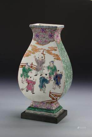 19th Century Famille Rose vase, in a four sided form, depicting four figures in a garden, with colorful glaze, and pattered accents, drilled.