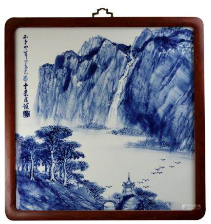 Chinese contemporary by Huang Mei Yao. blue and white plaque of a landscape, a forest, bridge and building in the foreground, next to a river, with tall mountains and waterfall in the background, surrounded by a wooden frame,