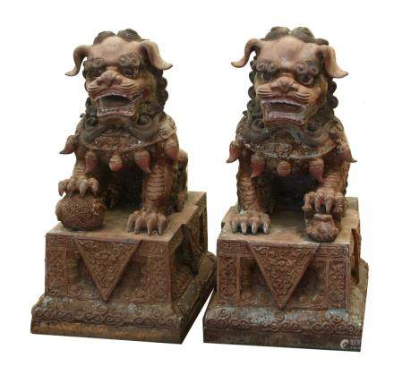 18th Century a pair of bronze foo lions, in seated position, each with a front paw resting on an object, intricately carved features, on raised bases carved with triangular designs.
