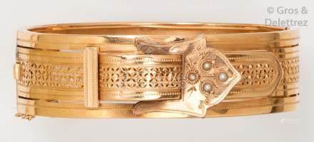 Bracelet rigide ouvrant en or jaune ciselé à décor d'une boucle sertie de demi-