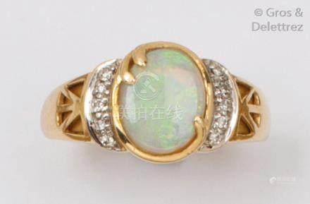 Bague en or jaune ornée d'un cabochon d'opale épaulé de diamants taillés en bri