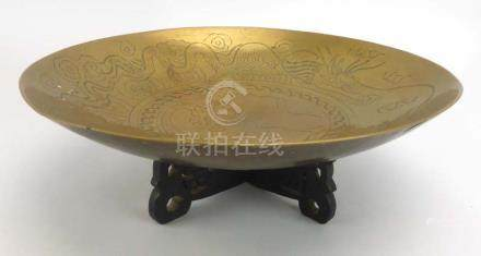 A Chinese brass 'singing' bowl decorated with a stylised dragon on a carved stand, d. 29.