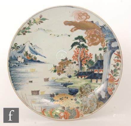 A large early 20th Century Japanese charger decorated with a gilt dragon looking over a garden and