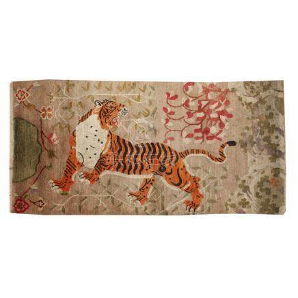 TIBETAN 'TIGER' RUGTIBET, 20TH CENTURY depicting a tiger striding and roaring, surrounded by