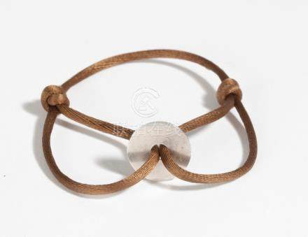 DINH VAN. Bracelet en cordelette de soie, orné d'un pendentif bi en argent mart