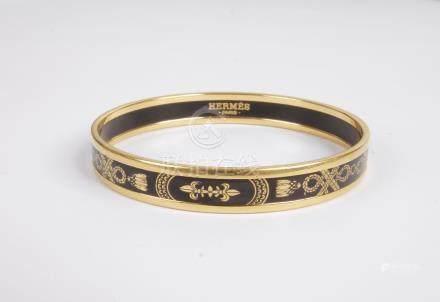 HERMÈS. Bracelet jonc en métal doré et émail noir orné de cordelettes et pompon