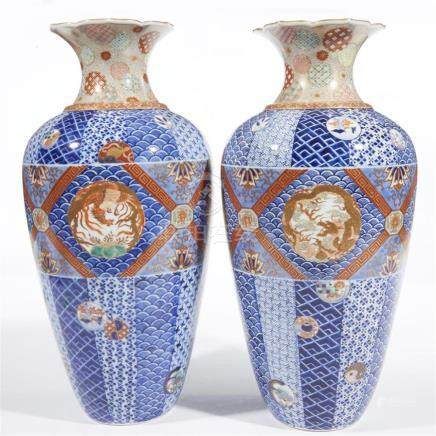 A pair of Japanese porcelain vases decorated in an Imari pal