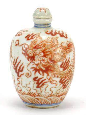 Chinese porcelain iron red snuff bottle with stopper, hand painted with a dragon amongst clouds,