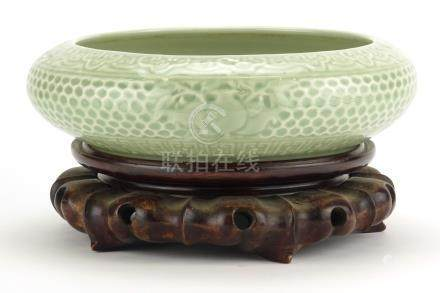 Chinese celadon glazed squatted bowl, raised on a carved wood stand, six figure character marks to