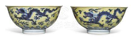 A RARE PAIR OF YELLOW-GROUND BLUE AND WHITE 'DRAGON' BOWLSKANGXI MARKS AND PERIOD