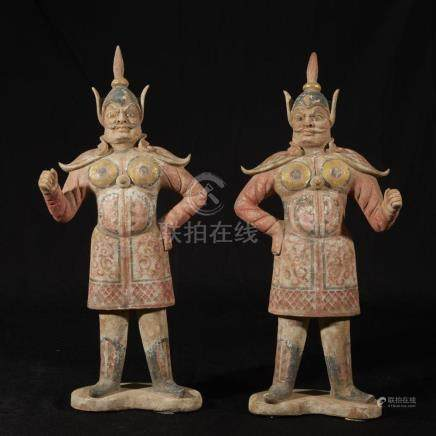 A pair of Chinese painted and parcel gilt pottery figures of