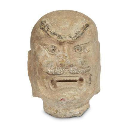 A carved and painted stone head of a guardian warrior, Tang