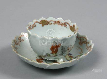 An 18c lotus moulded porcelain teabowl and saucer having chevron shaped borders and painted with