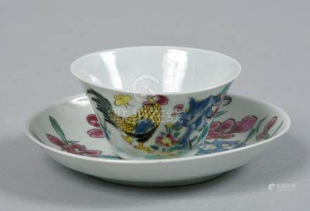 A small Chinese teabowl and saucer painted with flowers, cockerel and butterfly in bright enamel