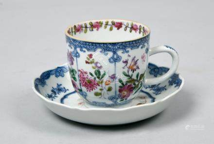 An 18c coffee cup and saucer decorated in underglaze blue and famille rose with a flower spray