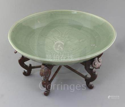 A Chinese Ming dynasty Longquan celadon dish, 15th century, with fine crazing to the glaze, the