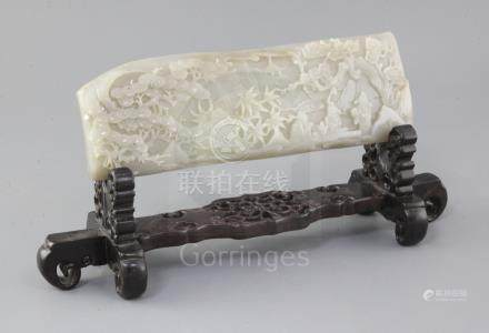 A Chinese pale grey jade plaque, carved in high relief with three sages seated at a table in a