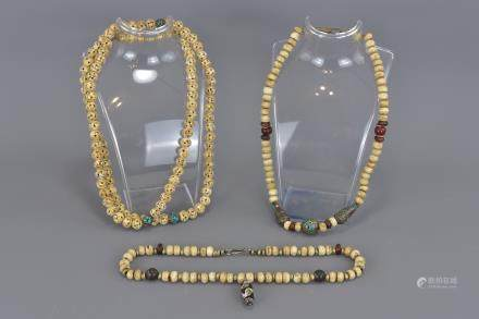 A group of three mala bead necklaces.