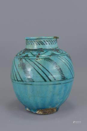 An Islamic Medieval turquoise glazed vase. 22cm height