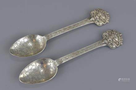 A pair of South East Asian mask head silver spoons. 14.5cm length