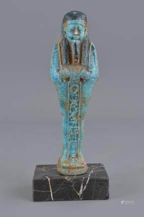 An Egyptian blue faience figure on marbel stand. 17cm height