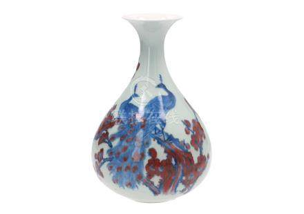 A blue and underglaze red porcelain vase, decorated with two peacocks on flower branches