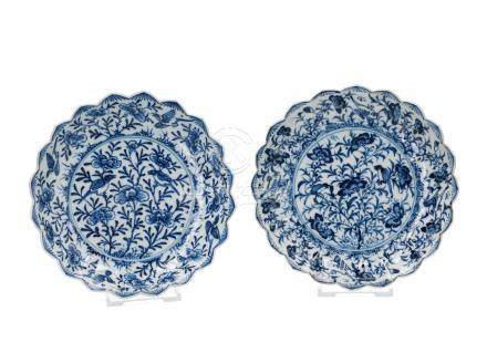 A pair of blue and white porcelain saucers with scalloped and ribbed rim, decorated with flowers and birds