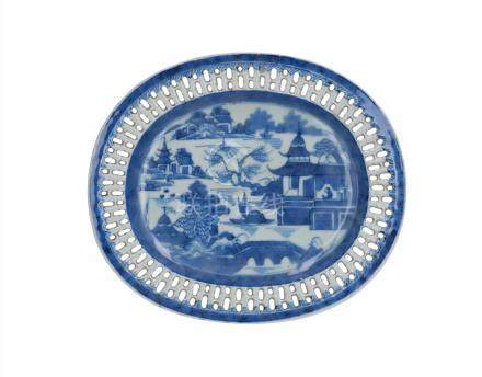An oval blue and white porcelain serving dish with open work rim, decorated with river landscape and buildings
