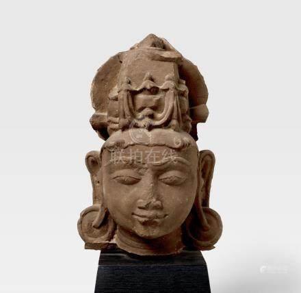 A RED SANDSTONE HEAD OF A VAISHNAVAITE DEITY NORTH INDIA, CIRCA 12TH CENTURY